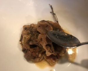 Cooked Jamaican Oxtail stew in a white bowl with a spoon. Meat is falling off the bone and connective tissue is broken down. The bones are separating; for Single Ingredient Groceries