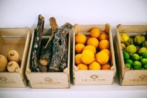 FOUR BROWN CRATE BOXES WITH SQUASH, FIRE WOOD, ORANGES, AND GREEN FRUITS - SINGLE INGREDIENT GROCERIES