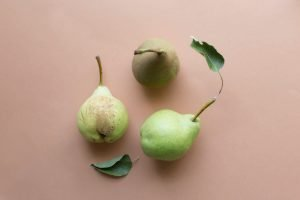 THREE GREEN PEARS WITH LEAVES ON PINK BACKGROUND - SINGLE INGREDIENT GROCERIES