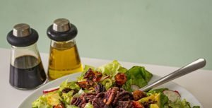 Oil and Vinegar in bottles next to a salad.