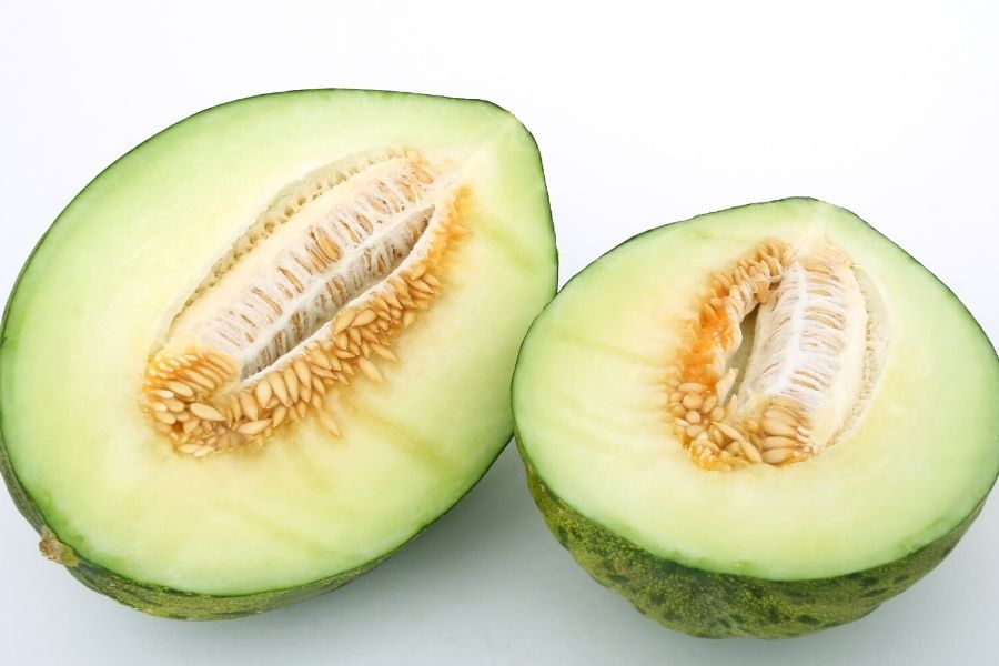GREEN MELON WITH LIGHT GREEN FLESH AND SEEDS CUT IN HALF ON WHITE BACKGROUND
