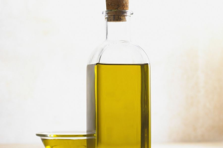 IMAGE OF YELLOW LIQUID IN A CLEAR TALL GLASS BOTTLE WITH SAME IMAGE IN SMALL GLASS BOWL FOR BLOG POST ABOUT WHITE BALSAMIC VINEGAR