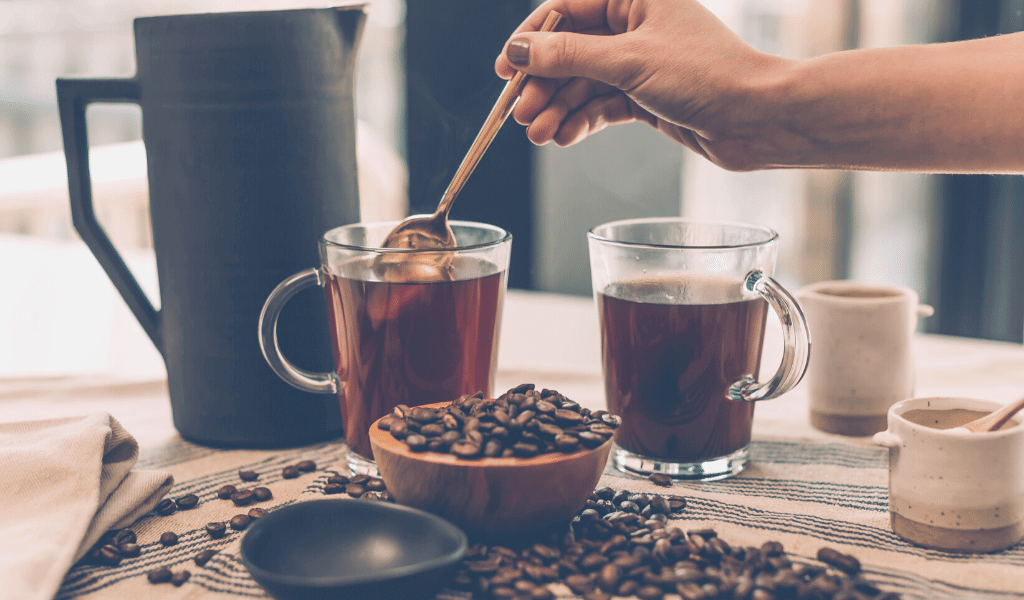 types of coffee in cups with coffee beans on a table