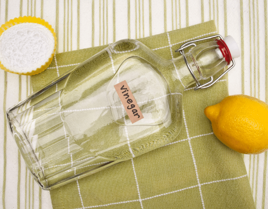white distilled vinegar for cleaning on a cloth with a lemon