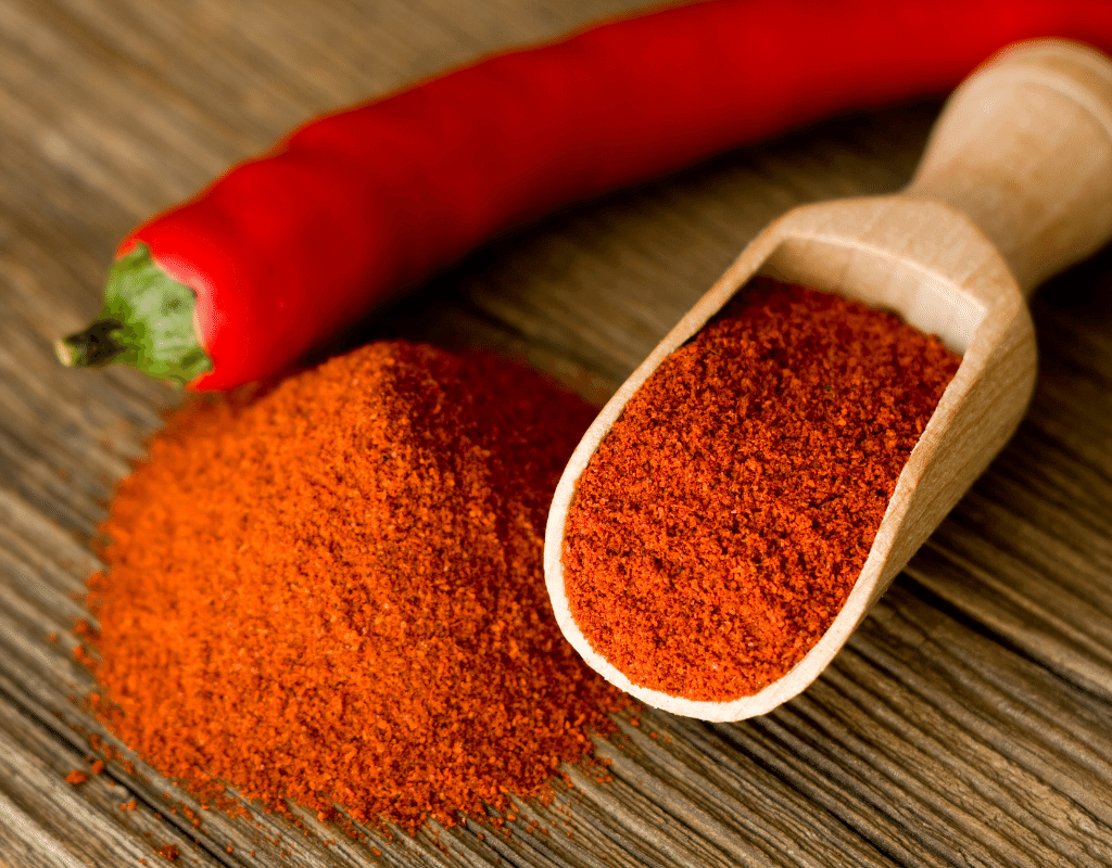 paprika powder in a spoon with a pepper on a table