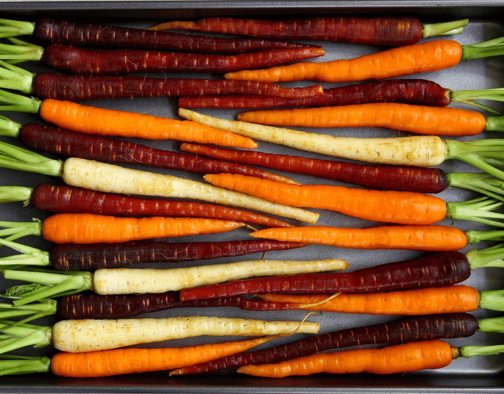 rainbow carrots on a tray. Orange, red, purple, and white carrots