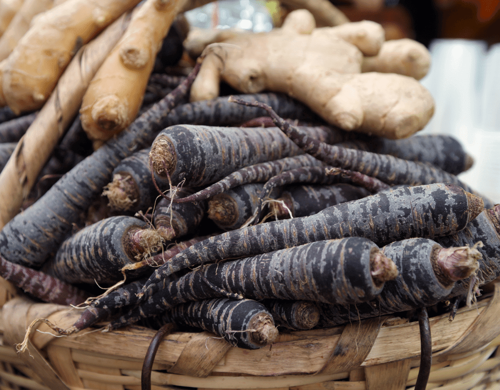 Ginger root and black carrots in a basket