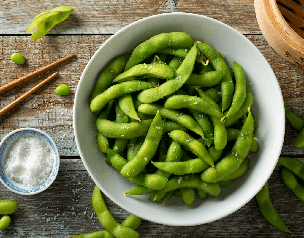 fresh green peas in a wooden bowl with peapods displayed on a wooden board. Peas are a starchy vegetable.