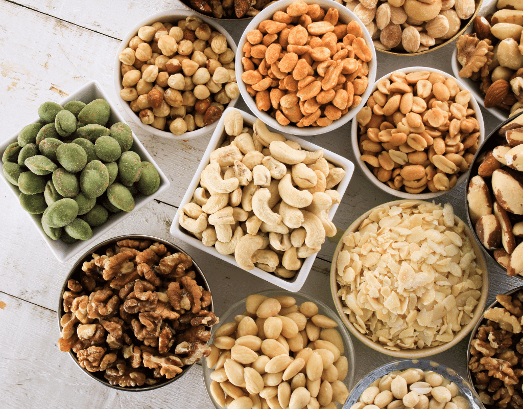 several types of nuts in small white dishes