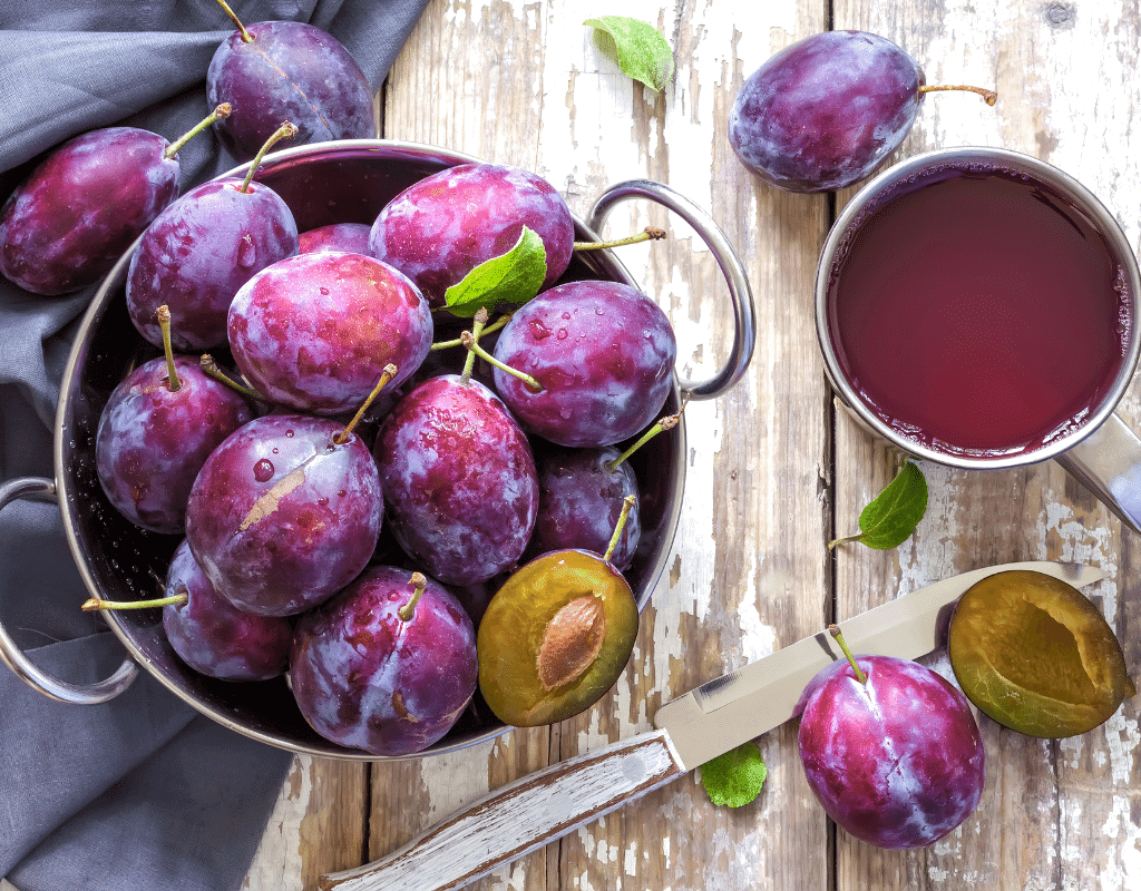bowl of plums displayed on a wood background
