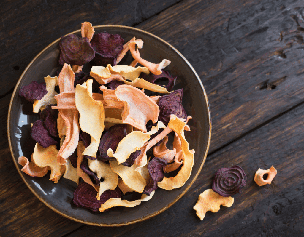 dehydrated veggie chips in a bowl on a dark wooden background