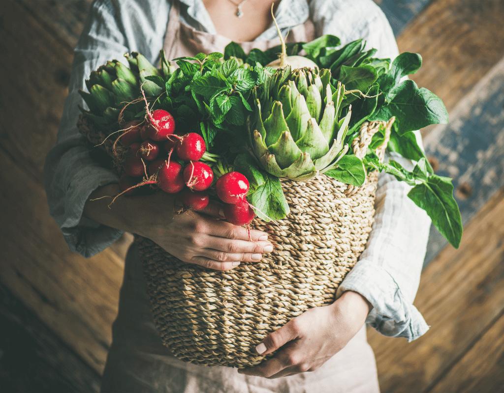 garden vegetables in a wicker basket held by a woman