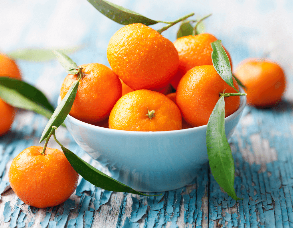 oranges in a blue bowl on a wood background