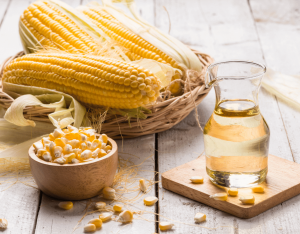 corn on the cob and corn oil in a clear bottle on a wooden background
