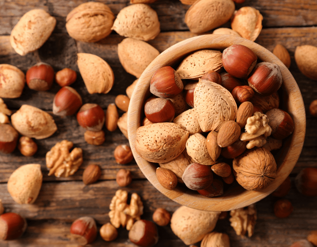 almonds, walnuts, and hazelnuts displayed in a wooden background