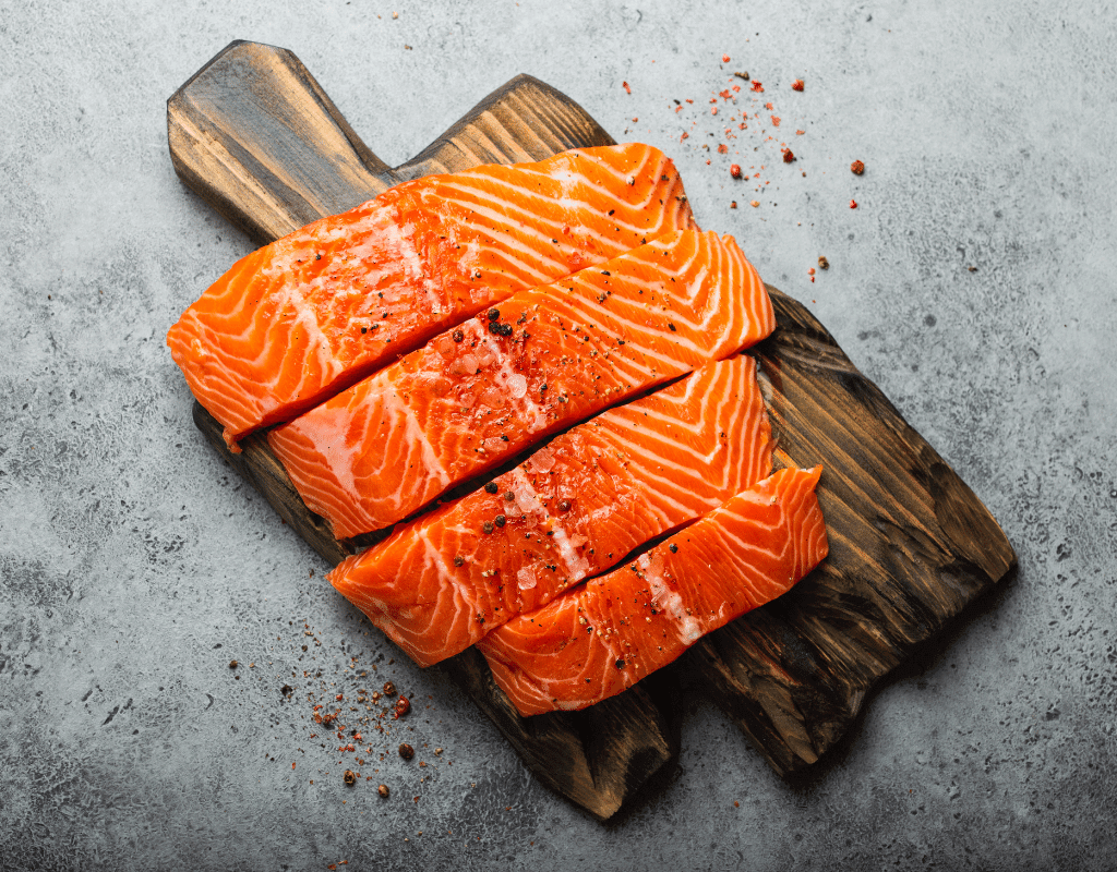 sliced fresh salmon on a wooden cutting board