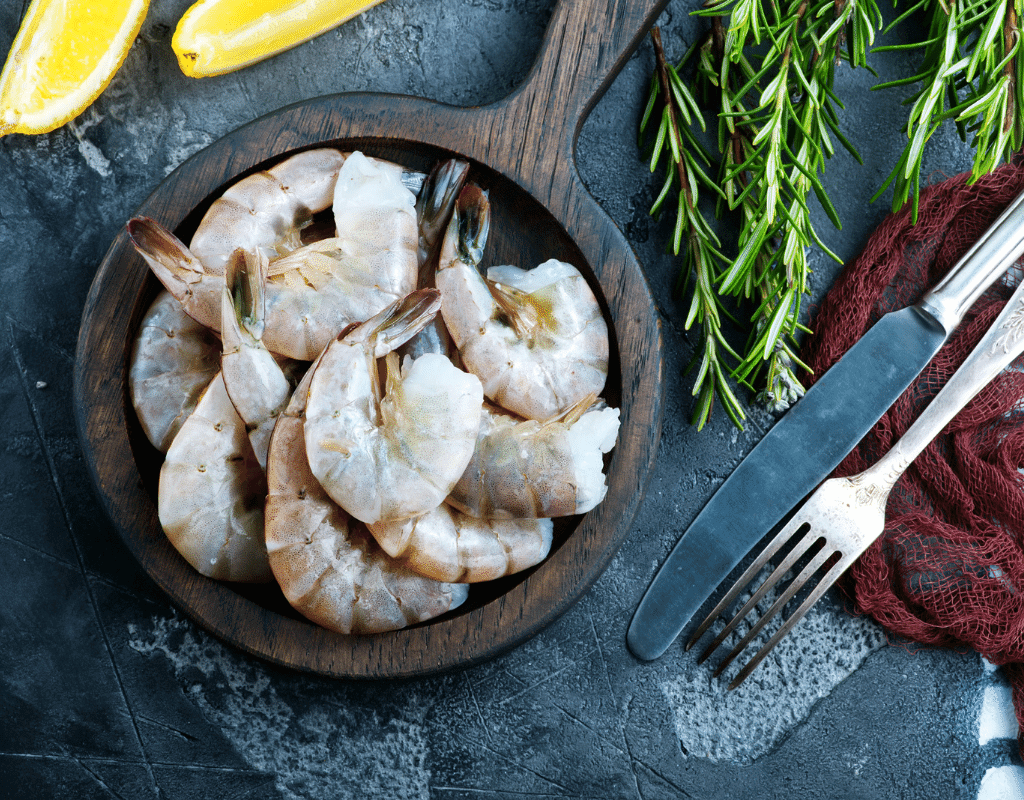 fresh raw shrimp in a wooden bowl on a slate background with rosemary sprigs, fork and knife displayed