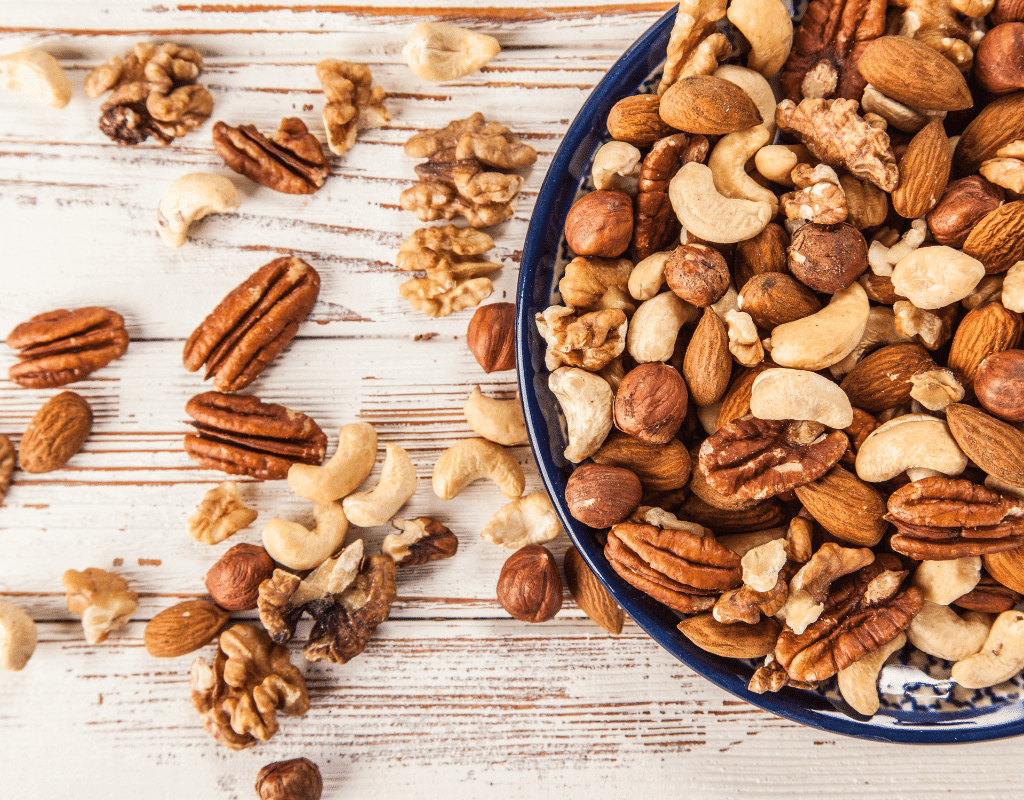 mixed tree nuts in a blue bowl on a white wood background