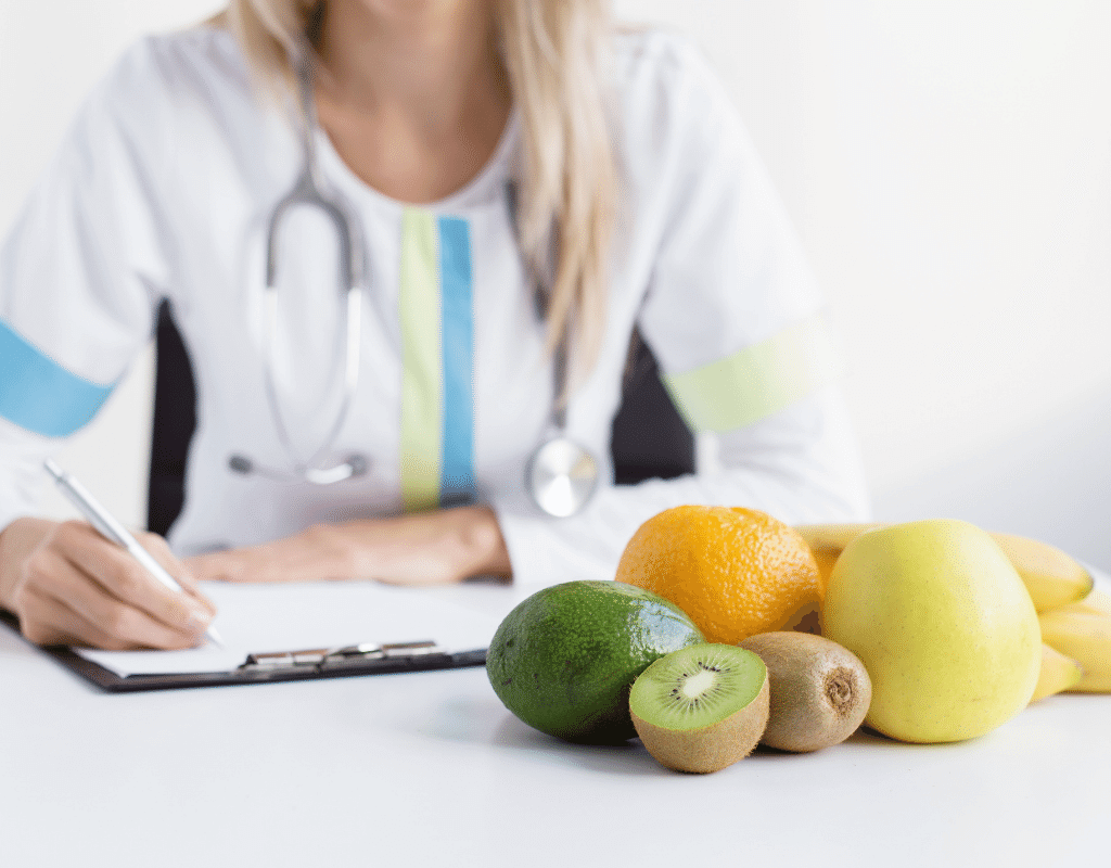 dietitian at a desk with fruit discussing a personalized therapeutic diet