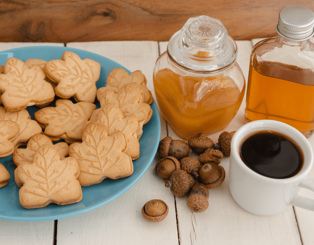 maple cookies, coffee, hazelnuts, maple syrup displayed on a blue plate on a white wooden background