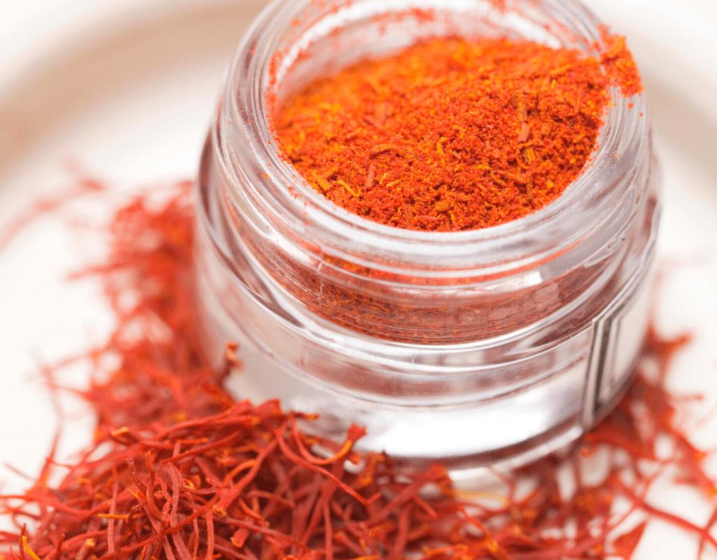 red saffron powder and saffron threads displayed on a white background
